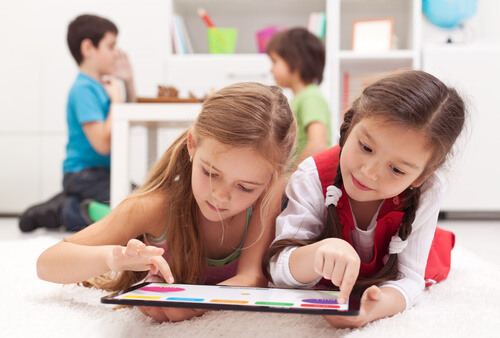 Little girls playing on a tablet computing device Little girls playing on a tablet computing device